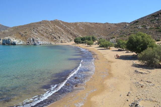 A praia é de areia branca e fina, com um mar limpo e claro com tons de verde e azul.