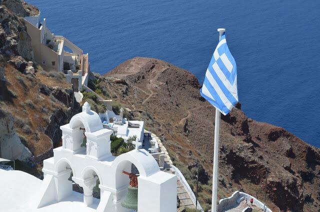 Casinha brancas com a bandeira da Grécia