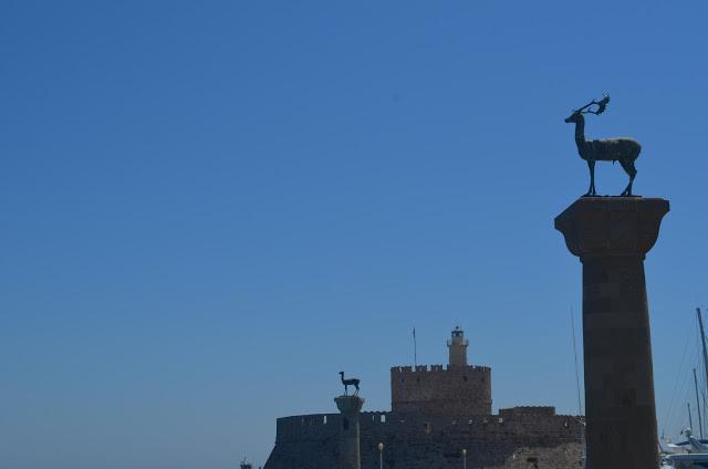 Torre com cervos no alto indicando o local do Colosso de Rodes