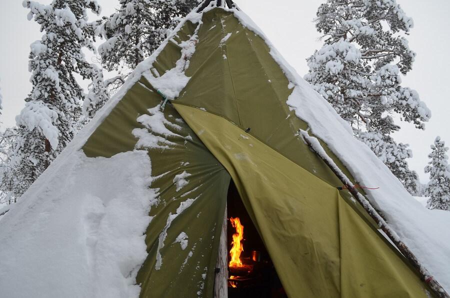 Cabana com fogueira e almoço no Lago Inari congelado na Lapônia Finlandesa
